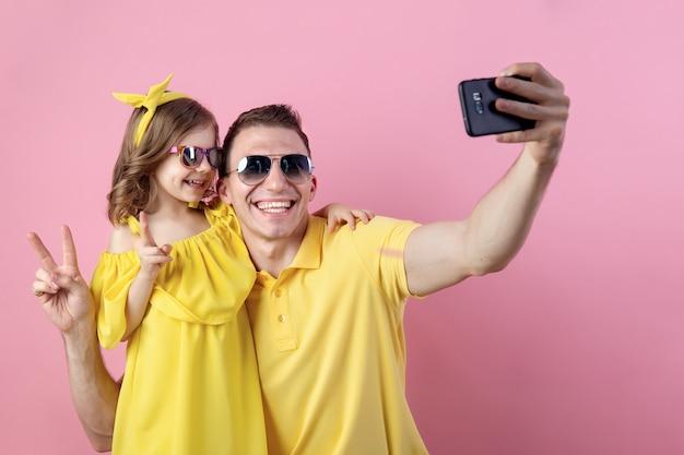 パパと小さな娘がスマートフォンでselfieを行う
