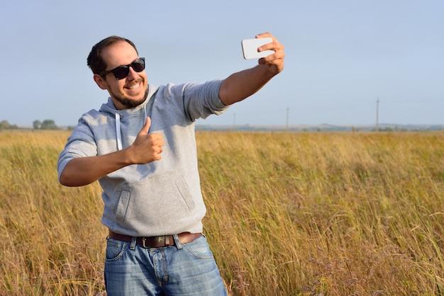 サングラスの男がフィールドでselfieを撮影します。