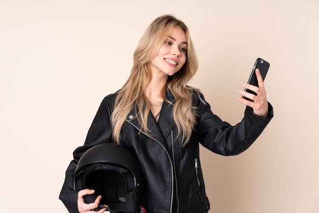Selfieを作るベージュの壁に分離されたオートバイのヘルメットを持つ金髪の女性
