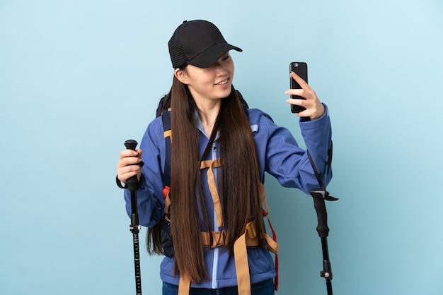 Selfieを作る青い壁の上のバックパックとトレッキングポールを持つ若い中国人の女の子