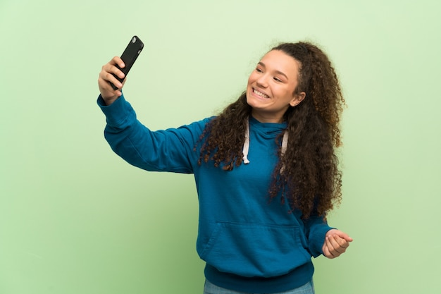Selfieを作る緑の壁の上のティーンエイジャーの女の子