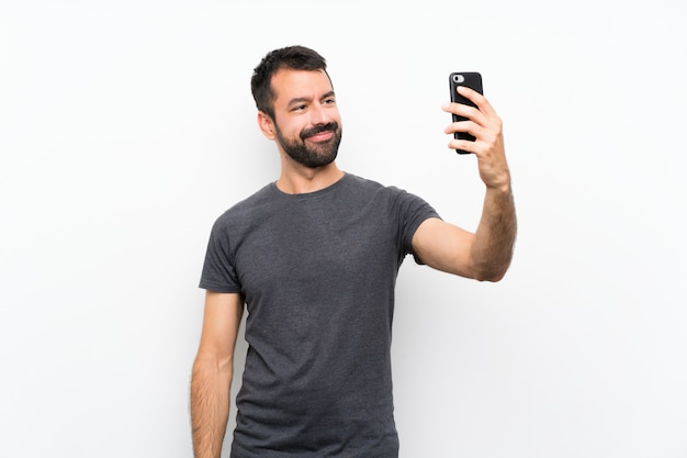 Selfieを作る分離白で若いハンサムな男