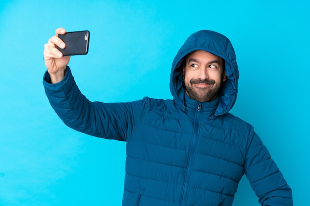 Укомплектуйте личным составом нося зимнюю куртку и держащ кофе на вынос над изолированной голубой стеной делая selfie