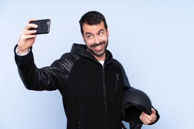 Selfieを作る孤立した壁の上のオートバイのヘルメットを持つ男