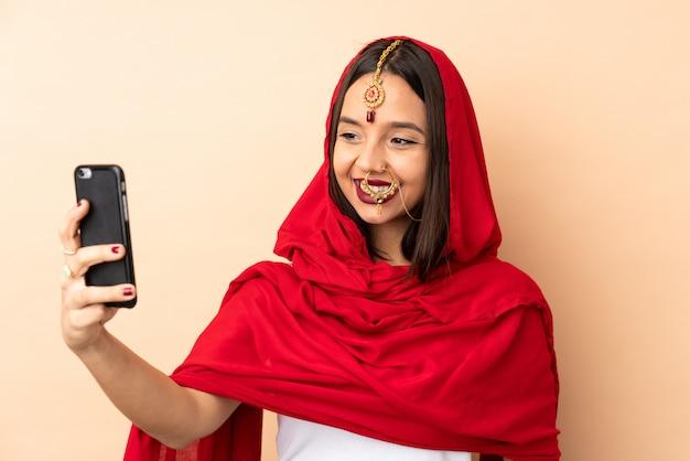 Selfieを作るベージュの壁に若いインド人女性