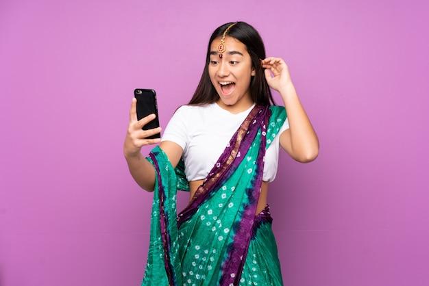 Selfieを作る壁の上のサリーと若いインド人女性