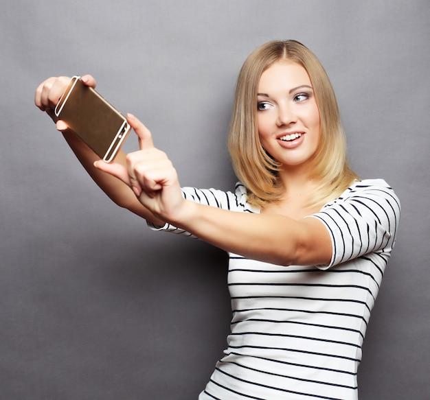 自分撮りの時間。彼女のスマートフォンでselfieを作るうれしそうな若い女性
