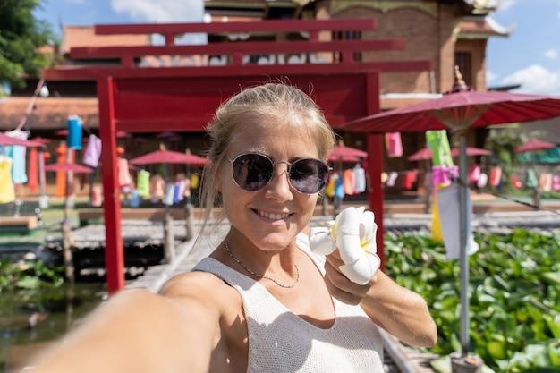 白いユリとselfieを作るサングラスを持つ女性
