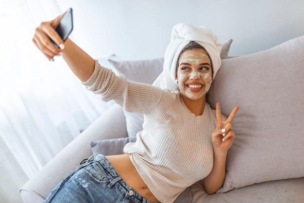 彼女のスマートフォンでselfieを作る顔の粘土マスクを持つ女性