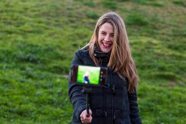 緑の壁を越えてスマートフォンとselfieスティックで写真を撮る美しい若い女性
