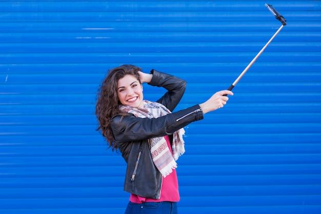 青い背景にスマートフォンでselfieを取って幸せな美しい女性。