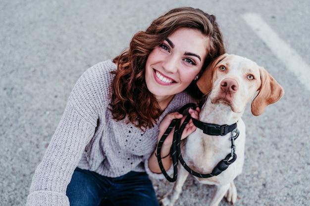 通りで彼女の犬と携帯電話でselfieを取る若い女性