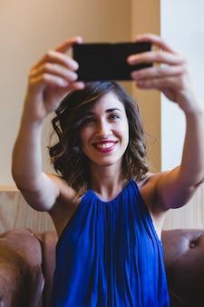 携帯電話でselfieを取ると笑顔の若い美しい女性。カジュアルな青いドレスを着ています。屋内、テクノロジー、ライフスタイル