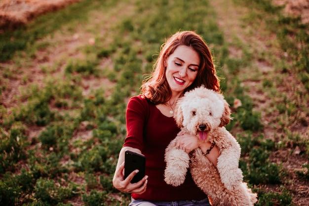 田舎の日没で彼女の犬とselfieを取って美しい白人女性。携帯電話を使用します。屋外でのテクノロジーとライフスタイル