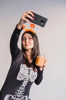 オレンジジュースを飲むと、携帯電話でselfieを取る若い美しい女性。黒と白のスケルトンコスチュームを着ています。ハロウィーンのコンセプト