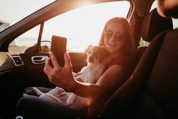 若い女性と夕暮れ時の車の中で彼女のかわいい犬。旅行のコンセプト。携帯電話でselfieを取る女性