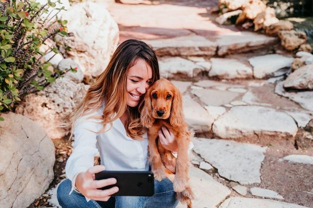 屋外のコッカースパニエルのかわいい子犬と、selfieを取る若い女性