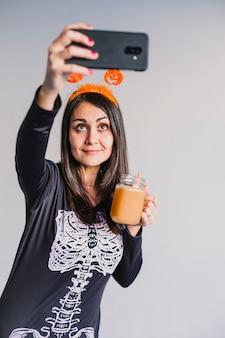 オレンジジュースを飲むと、携帯電話でselfieを取る若い美しい女性。黒と白のスケルトンコスチュームを着ています。ハロウィーンのコンセプト。屋内で