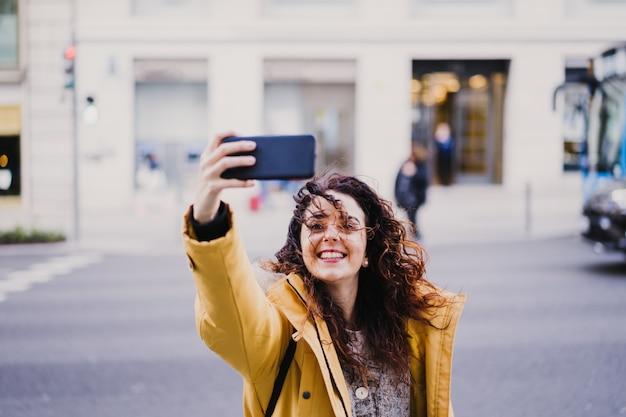 Молодая красивая туристическая женщина, принимая selfie на открытом воздухе на улице. счастливая женщина улыбается. концепция образа жизни и путешествий