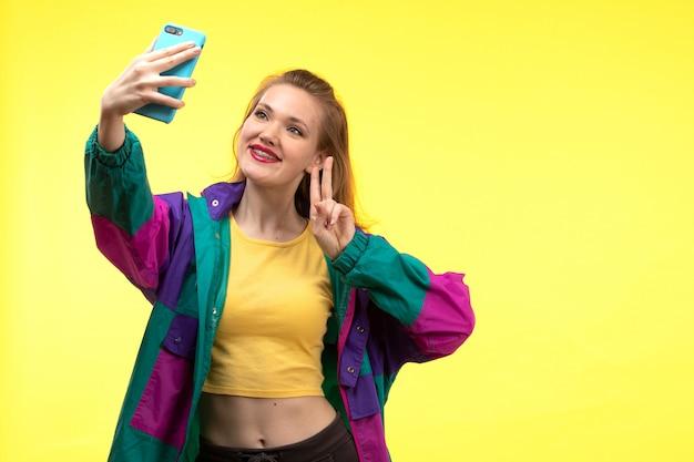 黄色いシャツの黒のズボンと携帯電話の幸せな表情でselfieを取ってカラフルなジャケットの正面の若い現代女性