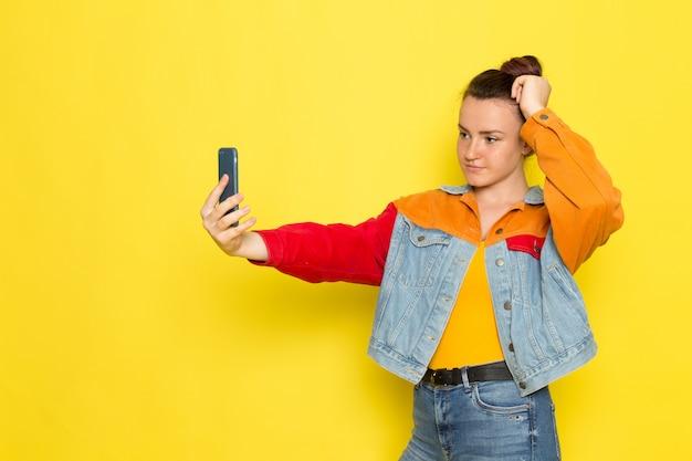 黄色いシャツのカラフルなジャケットとブルージーンズのポーズと、selfieを取って正面の若い女性