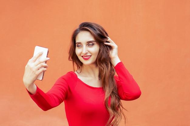 美しい大人の女の子は、オレンジ色の壁の背景にスマートフォンでselfieを取っています。
