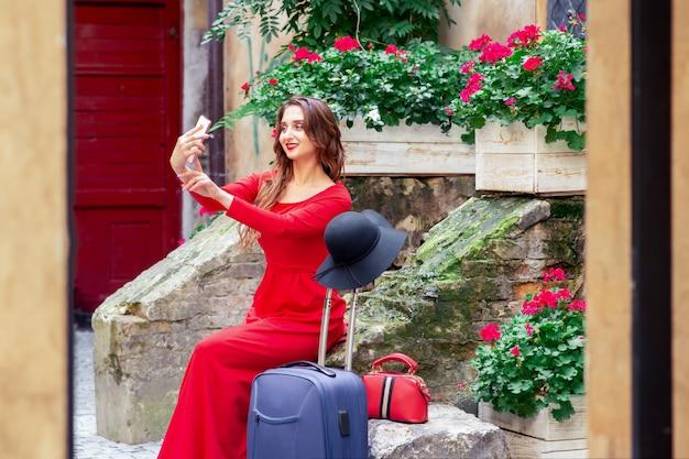 美しい観光ビジネスの女性は、スマートフォンでselfieを取っています。