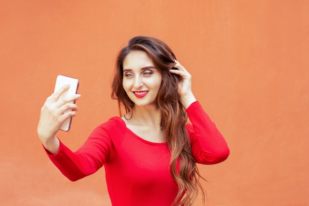 美しい大人の女の子は、オレンジ色の壁にスマートフォンでselfieを取っています