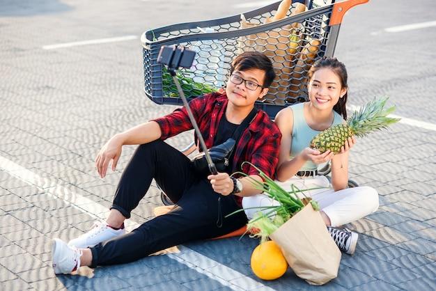 美しい少女と若い男は笑みを浮かべて、スーパーマーケットの店のカートでselfie写真を撮っています。コンセプトファミリーショッピング。