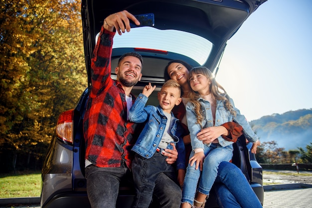 かわいい素敵な子供たちと幸せなスタイリッシュな親がトランクに座っている間スマートフォンで面白いselfieを作っています。幸せな現代家族の概念。