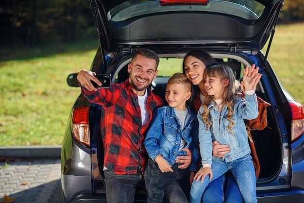 かわいい素敵な子供たちと幸せなスタイリッシュな両親は、トランクに座っている間スマートフォンで面白いselfieを作っています。