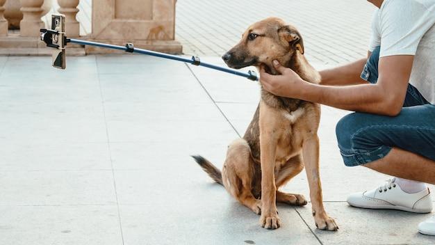 若い男は通り犬とselfieを取る