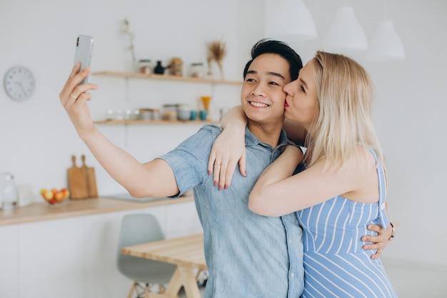 アジアの男性と彼の白人のブロンドの女性は一緒に時間を過ごし、キッチンでお互いにselfieを作る