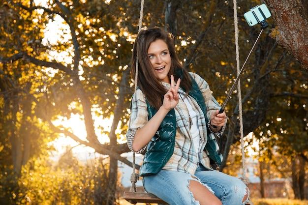 秋の公園でselfieを取る女性