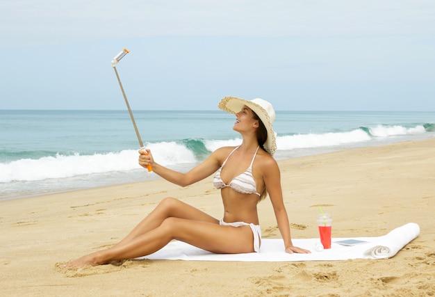 美しい女性は、ビーチでselfieを取っています。