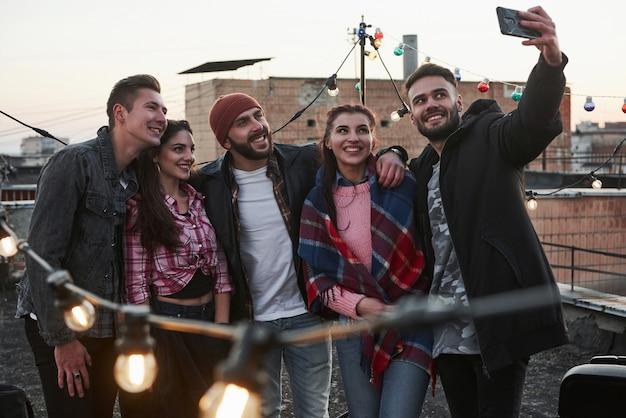 電話で見てください。楽しい若い陽気な友人のグループ、お互いをハグし、飾る電球で屋根の上でselfieを取る
