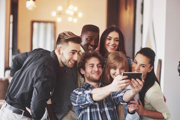 多民族の人々が携帯電話でselfieを取ってカフェで楽しんで
