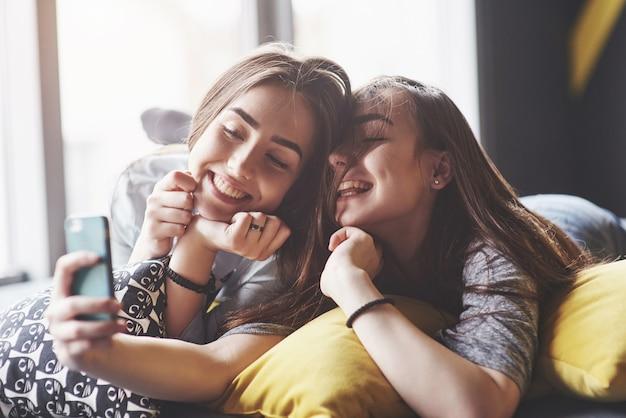 Две милые улыбающиеся близнецы сестры держа смартфон и делая selfie. женщины лежат на диване позируют и радуются