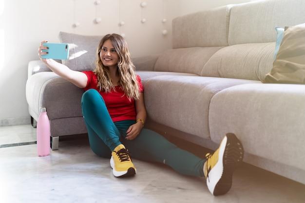 彼女のスマートフォンを自宅でselfieを取って床に座っている若いスポーティな女性