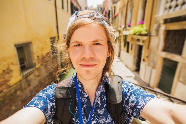 ヴェネツィアの運河の背景にselfieを取ってキャップでスタイリッシュな幸せな若い男。イタリアの幸せな観光客。ヨーロッパへ旅行します。クローズアップの肖像画。電話で自分撮りを取る。ヴェネツィアの観光。ベネチアン運河