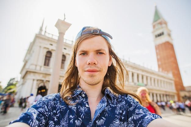 サンマルコ広場のヴェネツィアでselfieを取ってスタイリッシュな幸せな若い男。イタリアの幸せな観光客。ヨーロッパへ旅行します。