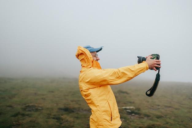 風の強い霧のフィールドでselfieを取って幸せな陽気な男。