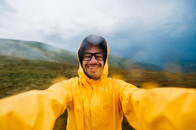 Улыбающийся путешественник человек в желтый плащ, принимая selfie в дождливых горах.