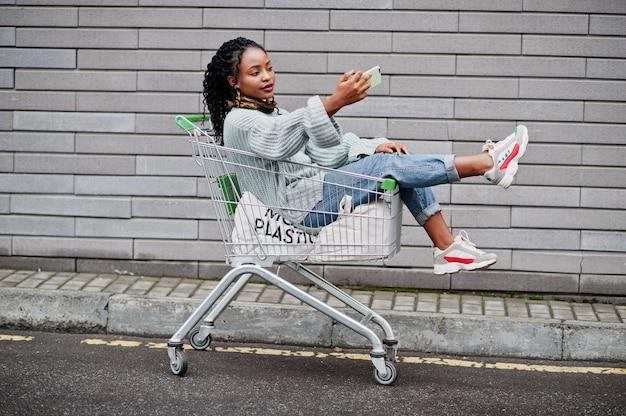 ショッピングカートのトロリーに座っているアフリカの女性は、屋外市場を提起し、電話でselfieを作っています。