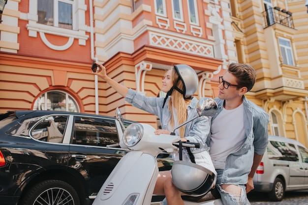 金髪の女性は彼女のボーイフレンドと一緒に自転車に座って、selfieを取って