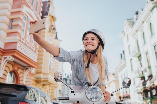 女性は座って、オートバイのコントロールに寄りかかって、selfieを取って