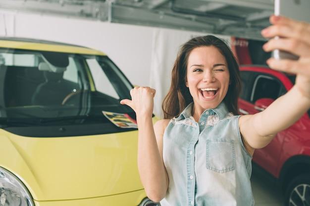 女性はショールームで新しい車でselfieを取る
