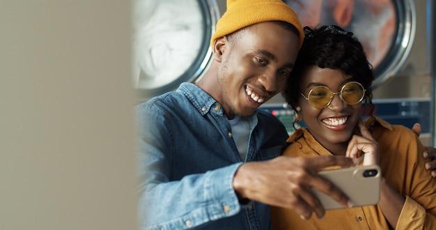 愛を抱いて、ランドリーサービスでselfie写真を撮りながらスマートフォンのカメラに笑顔で幸せなアフリカ系アメリカ人カップル。陽気な若い男と女が洗濯機で電話で写真を作る。