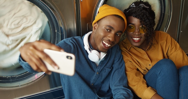 陽気なアフリカ系アメリカ人カップルがランドリーサービスでselfie写真を撮っている間、スマートフォンのカメラに笑顔します。幸せな魅力的な若い男と女が公共のコインランドリーで電話で写真を作ります。