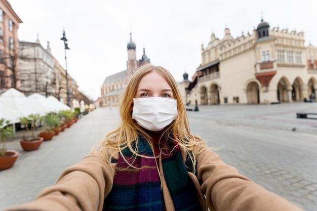 クラクフのマーケット広場にある有名な聖マリア大聖堂の前でselfie写真を作るマスクを持つスタイリッシュなブロンドの女性。コロナウイルスの流行の概念。市内の検疫